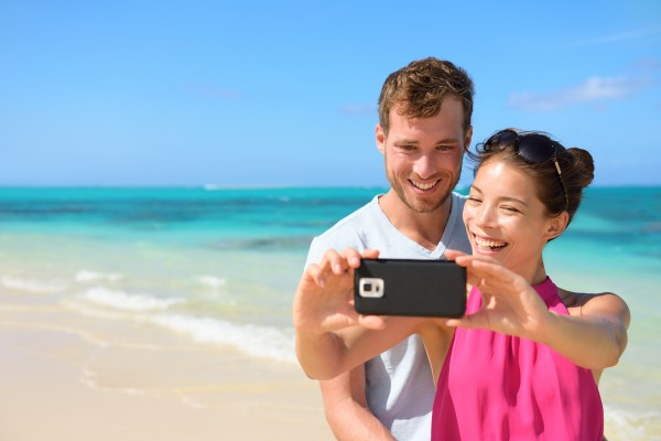 Smartphone - beach vacation couple taking selfie photograph using smartphone relaxing and having fun holding smart phone camera. Young beautiful multicultural Asian Caucasian couple on summer beach.